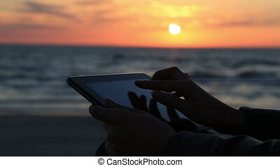 Close up woman hand using tablet at seaside on sunlight and background during sea and ocean sunset