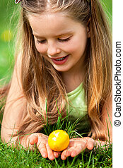 Satisfied girl is searching easter egg on green grass...