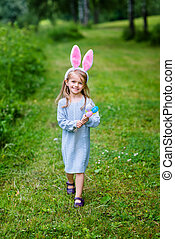Adorable little girl with long blond hair wearing rabbit or...