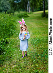 Smiling little girl with long blond hair wearing rabbit or...