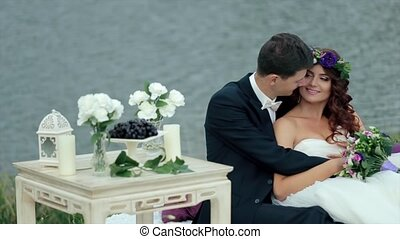 Just Married Couple Sitting Embraced Near a Pond - Bride and...