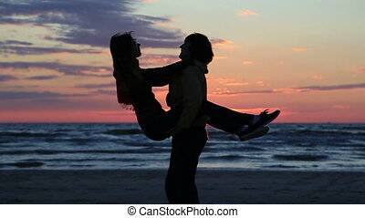 Fallen in love family pair dancing at sea sunset background