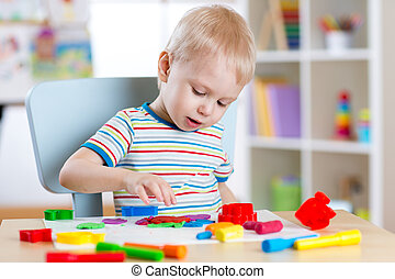 Kid boy playing with plasticine at home or kindergarten