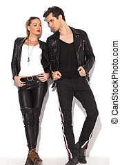young fashion couple in leather clothes looking at each...
