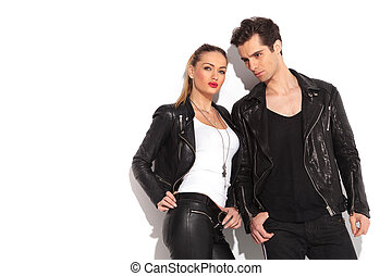 young fashion couple in leather clothes posing in studio,...