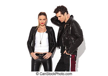 hot young couple in leather clothes, man with hands behind...