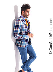 man standing with legs crossed in studio - smart casual man...