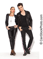young sexy couple in leather jackets posing, standing...