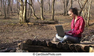 Woman working with laptop on the nature - Woman prints on...