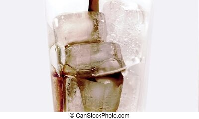 Coke Poured Over Ice Cubes In Glass - Rotating shot of...