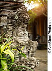 Traditional demon guard statue carved in stone on Bali,...