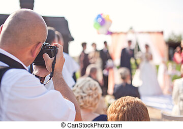 Photographer photographing a wedding ceremony
