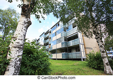 apartment block building with green lawn and trees -...