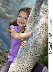 Girl swinging from a tree trunk - Cute young girl swinging...