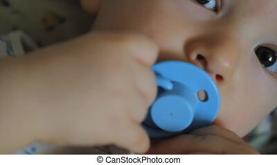 portrait of baby with blue pacifier, close-up