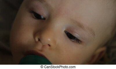 baby drinks juice from a bottle, close-up portrait HD