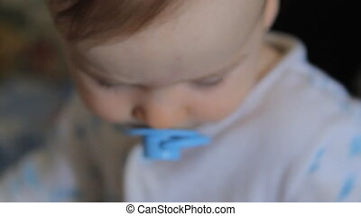 portrait of baby with blue pacifier