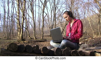 Woman with a laptop in the forest - Woman prints on the...