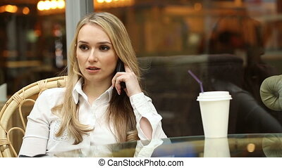 girl talking on the phone in a cafe. - quiet girl talking on...