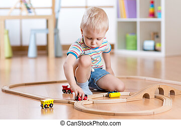 child boy playing with toys indoors at home - Cute child boy...