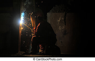 worker welding steel and sparks