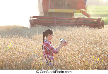 Agronomist in the field - Young woman agronomist looking at...