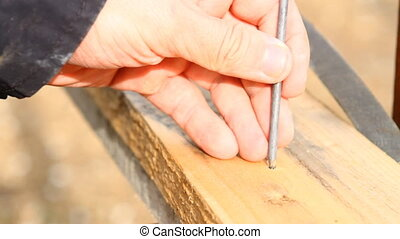 man hammers a nail into a plank, close-up