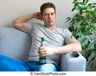 Man with bottle of beer watching sports on TV.