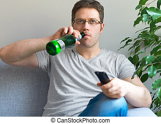 Man watching TV with bottle of beer
