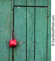 Wooden doors of the old toilet painted by green paint with...