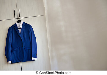Blue suit hanged to a wood closet in natural light