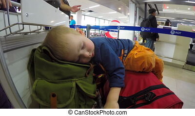 Boy Sleeping on the Luggage Bags in Airport - Little boy is...