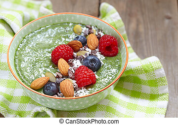 Green smoothie bowl with with berries, nuts and seeds...