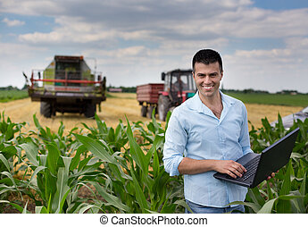 Businessman in the field - Young attractive farmer with...