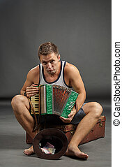 Portrait of a man with accordion sitting on retro suitcase...
