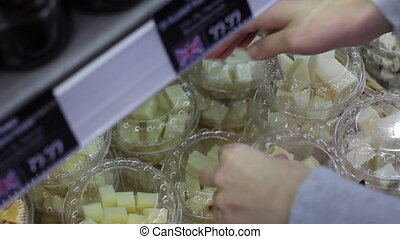 cheese cubes in plastic packaging - woman hans puts packages...