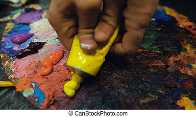 An artist squeezes out some yellow paint from a tube of oil...