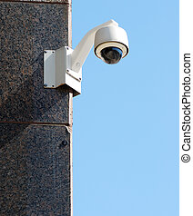 Security surveillance camera against a clear blue sky
