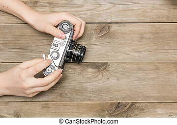 woman and 39;s hands holding a retro camera, view from above...