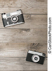 Two retro camera lying on the aged boards, flat lay