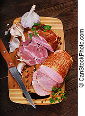 pieces of fresh smoked ham on rural background - pieces of...