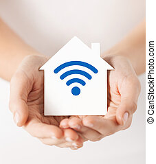 hands holding house with radio wave signal icon - people,...