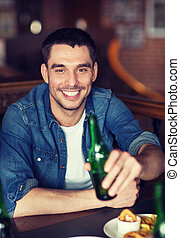 happy young man drinking beer at bar or pub - people,...
