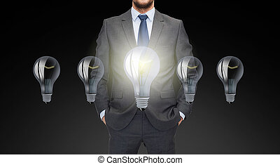 close up of businessman in suit with ligh bulbs - business,...