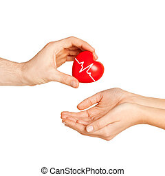 man hand giving red heart to woman - charity, health care,...