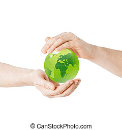 close up of hands holding green globe
