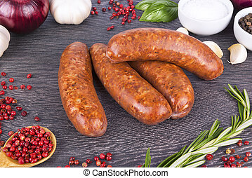 Raw sausage with spices on a dark wooden background.