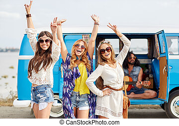 happy hippie friends having fun over minivan car - summer...