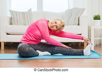 happy woman stretching leg on mat at home - fitness, sport,...