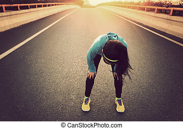 tired woman runner taking a rest after running hard on city...